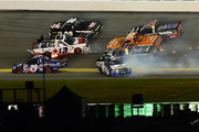 Rico Abreu, driver of the #98 Safelite Auto Glass Toyota, Cameron Hayley, driver of the #13 Cabinets by Hayley Toyota, Daniel Suarez, driver of the #51 ARRIS Toyota, and Ben Rhodes, driver of the #41 Alpha Energy Solutions Toyota, are involved in an on track incident during the NASCAR Camping World Truck Series NextEra Energy Resources 250 at Daytona International Speedway on February 19, 2016 in Daytona Beach, Florida.