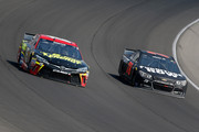 Clint Bowyer, driver of the #15 5-Hour Energy Toyota, races Martin Truex Jr., driver of the #78 Furniture Row/Visser Precision Chevrolet, during the NASCAR Sprint Cup Series Pure Michigan 400 at Michigan International Speedway on August 16, 2015 in Brooklyn, Michigan.