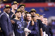 """Head coach Mike Krzyzewski of the Duke Blue Devils watches """"One Shining Moment"""" with his players Jahlil Okafor #15, Tyus Jones #5, Amile Jefferson, Grayson Allen, Marshall Plumlee #40, Quinn Cook #2 and Justise Winslow after defeating the Wisconsin Badgers during the NCAA Men's Final Four National Championship at Lucas Oil Stadium on April 6, 2015 in Indianapolis, Indiana. Duke defeated Wisconsin 68-63."""