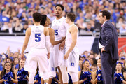 Jahlil Okafor #15 of the Duke Blue Devils reacts with teammates as head coach Mike Krzyzewski looks on in the second half against the Michigan State Spartans during the NCAA Men's Final Four Semifinal at Lucas Oil Stadium on April 4, 2015 in Indianapolis, Indiana.