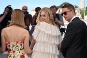 "US actress Elle Fanning (C) poses on May 20, 2016 with Australian actress Bella Heathcote (L) and Danish director Nicolas Winding Refn during a photocall for the film ""The Neon Demon"" at the 69th Cannes Film Festival in Cannes, southern France.  / AFP / ANNE-CHRISTINE POUJOULAT"