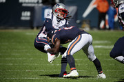 Stephon Gilmore #24 of the New England Patriots tackles Tarik Cohen #29 of the Chicago Bears in the second quarter at Soldier Field on October 21, 2018 in Chicago, Illinois.