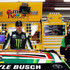 Kyle Busch, left, driver of the #18 Interstate Batteries Toyota, stands in the garage area during practice for the NASCAR Sprint Cup Series 5-Hour Energy 301 at New Hampshire Motor Speedway on July 18, 2015 in Loudon, New Hampshire. Busch is seen here wearing his NASCAR XFINITY Series firesuit.