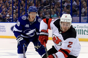 John Moore #2 of the New Jersey Devils and Ondrej Palat #18 of the Tampa Bay Lightning fight for the puck during Game Two of the Eastern Conference First Round  during the 2018 NHL Stanley Cup Playoffs at Amalie Arena on April 14, 2018 in Tampa, Florida.