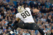Jimmy Graham #80 of the New Orleans Saints hurdles Roman Harper #41 of the Carolina Panthers during their game at Bank of America Stadium on October 30, 2014 in Charlotte, North Carolina.
