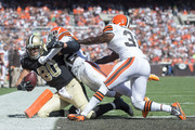 Tight end Jimmy Graham #80 of the New Orleans Saints scores a touchdown as he is tackled by cornerback Buster Skrine #22 and strong safety Donte Whitner #31 of the Cleveland Browns during the second half at FirstEnergy Stadium on September 14, 2014 in Cleveland, Ohio.