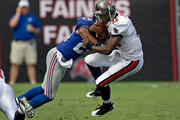 Quarterback Josh Johnson #11 of the Tampa Bay Buccaneers is tackled by defensive back Terrell Thomas #24 of the New York Giants during the game at Raymond James Stadium on September 27, 2009 in Tampa, Florida.