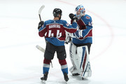 Goaltender Jonathan Bernier #45 of the Colorado Avalanche celebrates a win against the New York Islanders with teammate Mark Barberio #44 at the Pepsi Center on December 31, 2017 in Denver, Colorado. The Avalanche defeated the Islanders 6-1.