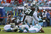 Running back Chris Ivory #33 of the New York Jets leaps over defenders in the second quarter during a game against the Miami Dolphins at Sun Life Stadium on December 28, 2014 in Miami Gardens, Florida.
