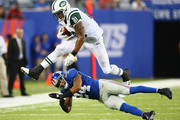 Kellen Winslow #81 of the New York Jets leaps over  Terrell Thomas #24 of the New York Giants during their pre season game at MetLife Stadium on August 24, 2013 in East Rutherford, New Jersey.