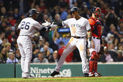 Aaron Hicks #31 of the New York Yankees celebrates with Andrew McCutchen #26 after hitting a three run home run during the fourth inning against the Boston Red Sox at Fenway Park on September 28, 2018 in Boston, Massachusetts.