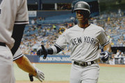 TAMPA, FL  SEPTEMBER 24: Andrew McCutchen #26 of the New York Yankees prepares to shake a teammates hand after scoring his second run in the seventh inning of the game against the Tampa Bay Rays at Tropicana Field on September 24, 2018 in St. Petersburg, Florida.