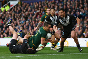 Cooper Cronk of Australia scores his sides second try as Kevin Locke (R) and Dean Whare (R) of New Zealand fail to challenge during the Rugby League World Cup Final between Australia and New Zealand at Old Trafford on November 30, 2013 in Manchester, England.