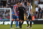 Referee Mike Dean separates Damien Delaney of Crystal Palace and Aleksandar Mitrovic of Newcastle United during the Barclays Premier League match between Newcastle United and Crystal Palace at St James' Park on April 30, 2016 in Newcastle upon Tyne, England.