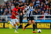 Hatem Ben Arfa of Newcastle United is closed down by Shinji Kagawa of Manchester United during the Barclays Premier League match between Newcastle United and Manchester United  at St James' Park on April 5, 2014 in Newcastle upon Tyne, England.