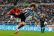 Patrice Evra of Manchester United and Fabrizio Coloccini of Newcastle United battle for the ball during the Barclays Premier League match between Newcastle United and Manchester United  at St James' Park on April 5, 2014 in Newcastle upon Tyne, England.