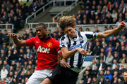 Fabricio Coloccini (R) of Newcastle in action with Patrice Evra of Manchester United during the Barclays Premier League match between Newcastle United and Manchester United at St James' Park on April 5, 2014 in Newcastle upon Tyne, England.