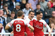 Granit Xhaka of Arsenal celebrates with teammates after scoring his team's first goal during the Premier League match between Newcastle United and Arsenal FC at St. James Park on September 15, 2018 in Newcastle upon Tyne, United Kingdom.