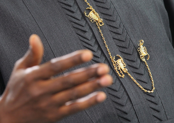 Nigerian President Goodluck Jonathan wears a chain of golden scorpions as he gestures while speaking to the media after talks with German Chancellor Angela Merkel at the Chancellery on April 19, 2012 in Berlin, Germany. The two leaders discussed economic cooperation between their two countries as well as security issues.