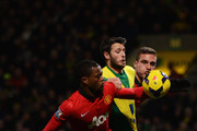 Patrice Evra of Manchester United appears to handle the ball as he is challenged by Wes Hoolahan of Norwich City during the Barclays Premier League match between Norwich City and  Manchester United at Carrow Road on December 28, 2013 in Norwich, England.