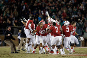 Players on the Stanford Cardinal, including Solomon Thomas #90, celebrate after Conrad Ukropina #34 of the Stanford Cardinal kicked a game-winning field at the end of regulation to beat the Notre Dame Fighting Irish at Stanford Stadium on November 28, 2015 in Palo Alto, California.