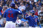 Javier Baez #9 (R) of the Chicago Cubs high fives Anthony Rizzo #44 after both scored runs against the Oakland Athletics during the first inning of the spring training game at Sloan Park on February 28, 2018 in Mesa, Arizona.
