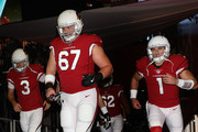 Center Tony Bergstrom #67 (C) of the Arizona Cardinals runs onto the field with Carson Palmer #3 (L) and Trevor Knight #1 (R) before the NFL game against the Oakland Raiders at the University of Phoenix Stadium on August 12, 2017 in Glendale, Arizona. The Cardinals defeated the Raiders 20-10.
