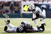 Chris Ivory #33 of the New York Jets avoids a tackle attempt by  T.J. Carrie #38 of the Oakland Raiders in the second quarter at MetLife Stadium on September 7, 2014 in East Rutherford, New Jersey.