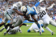 Melvin Gordon #28 of the Los Angeles Chargers is hit short of the goal line by Marquel Lee #55 and Marcus Gilchrist #31 of the Oakland Raiders during the second quarter at StubHub Center on October 7, 2018 in Carson, California.