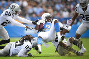 Running back Melvin Gordon #28 of the Los Angeles Chargers is tackled by linebacker Marquel Lee #55 of the Oakland Raiders, free safety Reggie Nelson #27, and defensive back Leon Hall #29 in the first quarter at StubHub Center on October 7, 2018 in Carson, California.