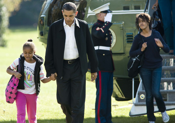 US President Barack Obama holds the hand of his daughter Sasha as daughter Malia (R) walks off Marine One to the White House November 8, 2009 in Washington, DC. The Obamas were returning from spending the night at Camp David.