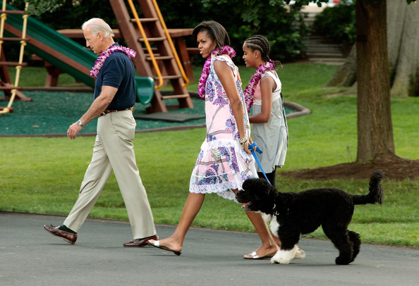 (AFP OUT) (L-R) U.S. Vice President Joe Biden, first lady Michelle Obama, Malia Obama and family dog Bo arrive at a luau for members of Congress and their families on the South Lawn of the White House June 25, 2009 in Washington, DC. In a celebration of the president's home state, the South Lawn was decorated with tiki torches and palm huts and the meal prepared by famous Hawaiian chef Alan Wong.
