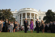 U.S. President Barack Obama, first lady Michelle Obama, Vice President Joseph Biden, his wife Jill Biden, and White House staff observe a moment of silence to mark the 12th anniversary of the 9/11 attacks,  September 11, 2013 on the South Lawn of the White House in Washington, DC. The nation is commemorating the anniversary of the 2001 attacks which resulted in the deaths of nearly 3,000 people after two hijacked planes crashed into the World Trade Center, one into the Pentagon in Arlington, Virginia and one crash landed in Shanksville, Pennsylvania.