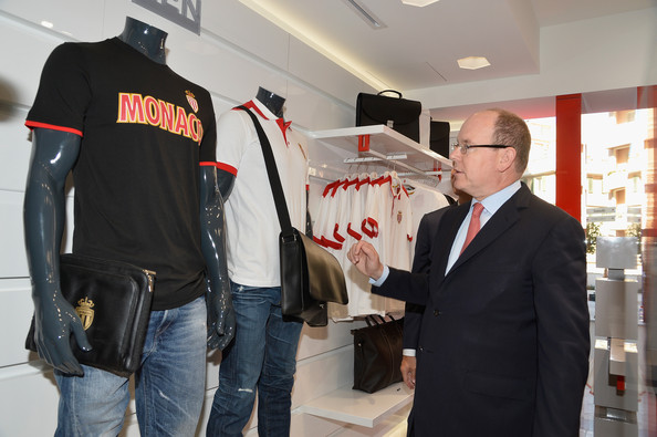 Prince Albert II of Monaco looks at merchandise as he attends the AS Monaco football club flagship store opening on July 31, 2014 in Monaco, Monaco.