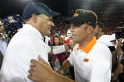 (L-R) Head coaches head coach Rich Rodriguez of the Arizona Wildcats and Mike Gundy of the Oklahoma State Cowboys greet following the college football game at Arizona Stadium on September 8, 2012 in Tucson, Arizona. The Wildcats defeated the Cowboys 59-38.