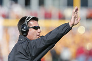 Head coach Mike Gundy of the Oklahoma State Cowboys signals a play from the sidelines during the second half of play against the Iowa State Cyclones at Jack Trice Stadium on October 26, 2013 in Ames, Iowa. The Oklahoma State Cowboys defeated the Iowa State Cyclones 58-27.