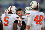 Head coach Mike Gundy of the Oklahoma State Cowboys talks to members of this team during a timeout against the Kansas Jayhawks in the third quarter at Memorial Stadium on October 11, 2014 in Lawrence, Kansas.  Oklahoma State  won the game 27-20.