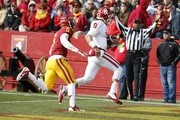 Quarterback Trevor Knight #9 of the Oklahoma Sooners runs the ball into the end zone for a touchdown in the quarter half of play as defensive back Kamari Cotton-Moya #5 of the Iowa State Cyclones defends at Jack Trice Stadium on November 1, 2014 in Ames, Iowa.