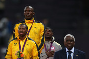 Silver medalist Yohan Blake of Jamaica, gold medalist Usain Bolt of Jamaica and bronze medalist Justin Gatlin of the United States stand alongside IAAF President Lamine Diack on the podium during the medal ceremony for the Men's 100m final on Day 10 of the London 2012 Olympic Games at the Olympic Stadium on August 6, 2012 in London, England.