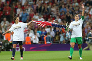 Hope Solo #1 and Carli Lloyd #10 of the United States celebrate with the American flag after defeating Japan by a score of 2-1 to win the Women's Football gold medal match on Day 13 of the London 2012 Olympic Games at Wembley Stadium on August 9, 2012 in London, England.