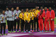 Gold medalists Yohan Blake, Usain Bolt, Nesta Carter and Michael Frater of Jamaica (C), silver medalists Trell Kimmons, Justin Gatlin, Tyson Gay and Ryan Bailey of United States (L) and bronze medalists Keston Bledman, Marc Burns, Emmanuel Callender and Richard Thompson of Trinidad and Tobago celebrate on the podium during the medal ceremony for the Men's 4 x 100m Relay Final on Day 15 of the London 2012 Olympic Games at Olympic Stadium on August 11, 2012 in London, England.