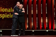 (L-R) Jury President Tom Tykwer and Festival director Dieter Kosslick hug each other on stage at the Opening Ceremony & 'Isle of Dogs' premiere during the 68th Berlinale International Film Festival Berlin at Berlinale Palace on February 15, 2018 in Berlin, Germany.