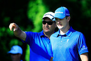 Justin Rose of England talks with caddie Mark Fulcher during a practice round prior to the start of the 95th PGA Championship at Oak Hill Country Club on August 6, 2013 in Rochester, New York.