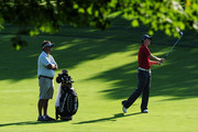 Justin Rose of England (R) hits a shot alongside his caddie Mark Fulcher during the third preview day of the 91st PGA Championship at Hazeltine National Golf Club on August 12, 2009 in Chaska, Minnesota.