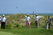 Webb Simpson (C) and Bubba Watson (2nd R) of the United States gesture after Simpson hits off the sixth tee as Ernie Els of South Africa (L) looks on during Round One of the 94th PGA Championship at the Ocean Course on August 9, 2012 in Kiawah Island, South Carolina.