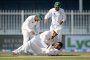 Shoaib Malik of Pakistan celebrates with captain Misbah-ul-Haq after dismissing England captain Alastair Cook during day five of the 3rd Test between Pakistan and England at Sharjah Cricket Stadium on November 5, 2015 in Sharjah, United Arab Emirates.