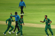 Wahab Riaz (R) of Pakistan celebrates with Muhammad Rizwan (L) and Shoaib Malik (C) taking the wicket of Marlon Samuels of West Indies during the third One Day International match between Pakistan and West Indies at Zayed Cricket Stadium on October 5, 2016 in Abu Dhabi, United Arab Emirates.
