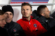 David Beckham (red top) of PSG is pictured on the bench prior to the Ligue 1 match between Paris Saint-Germain FC and Olympique de Marseille at Parc des Princes on February 24, 2013 in Paris, France.