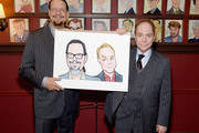 Penn Jillette and Teller pose with their Sardi's Caricatures at Sardi's on July 1, 2015 in New York City.