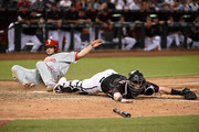 Chris Herrmann #10 of the Arizona Diamondbacks stretches to catch a throw while keeping his toe on home plate to get a force out as Daniel Nava #25 of the Philadelphia Phillies slides into home during the seventh inning at Chase Field on June 24, 2017 in Phoenix, Arizona.